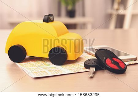 Yellow toy taxi, smartphone, car key and map on wooden table