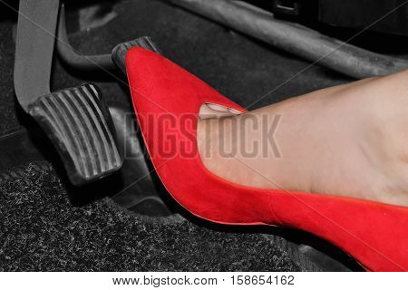Female foot with red shoe pushing on pedal of car