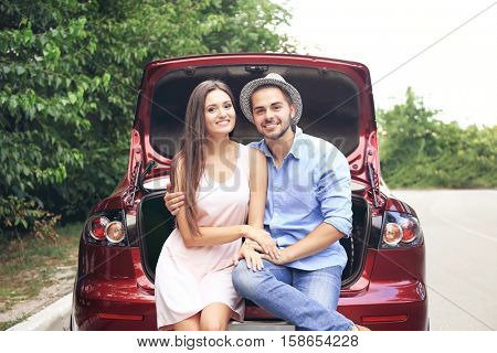 Beautiful young couple sitting in car trunk