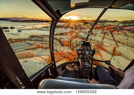 Helicopter cockpit flies in Bay of Fires, east coast of Tasmania in Australia, with pilot arm and control board inside the cabin.
