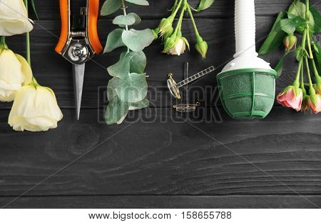Beautiful flowers and florist equipment on blue wooden background