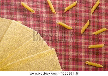 Lasagne sheets and penne pasta background. Flat lay. Top view. Close up. Food background concept.