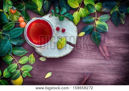 Tea in a transparent glass mug among the leaves on a brown wooden background