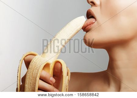 Sexy girl licking ripe and delicious banana. Contraception. Pleasure.