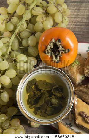 Eastern breakfast. Green tea with sweeties persimmon grapes on wooden surface with free space.