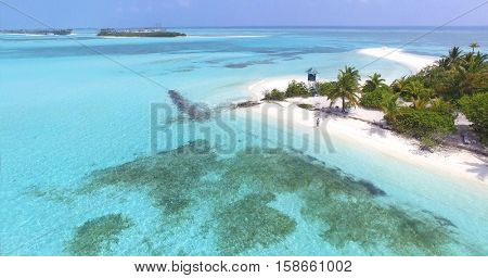 Panoramic landscape seascape aerial view over a Maldives Male Atoll island. White sandy beach with lifeguard tower seen from above