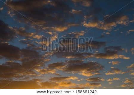 Sky with gold clouds - dramatic sunset beautiful natural background. Setting sun illuminates the clouds. Sunsets of Fijii.