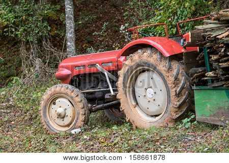 Old red tractor with trailor loaded with wood in autumnal forest