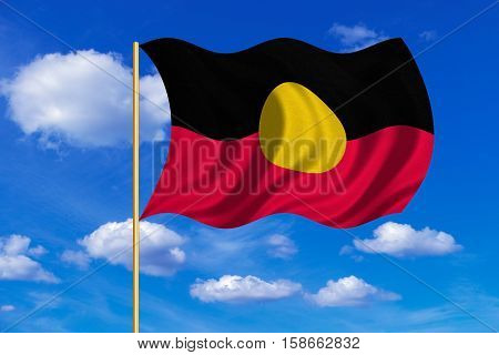 Australian Aboriginal official flag. Commonwealth of Australia patriotic symbol banner. Correct colors. Australian Aboriginal flag on flagpole waving in the wind blue sky background. Fabric texture. 3D rendered illustration