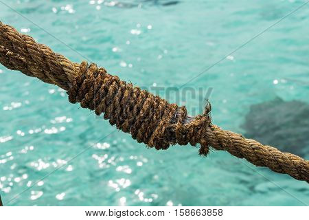 Old brown rope close-up in front of turquoise ocean on a sunny day in Maldives, Raa Atoll.