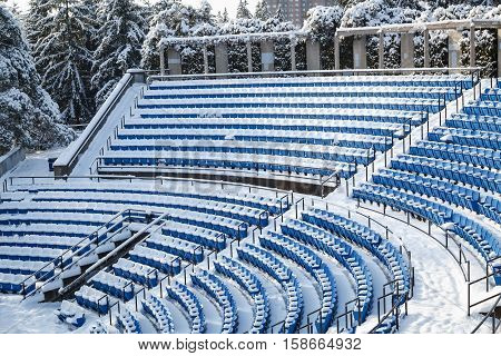Fragment of view of outdoor empty amphitheater rows of blue plastic seats covered in snow at winter time on sunny day