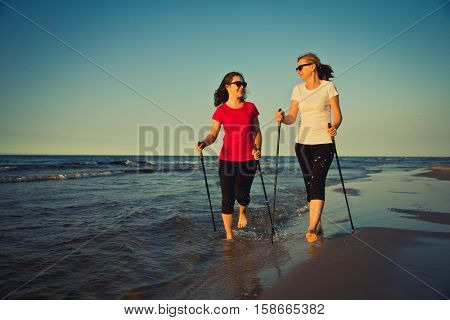 Nordic walking - two women working out on beach