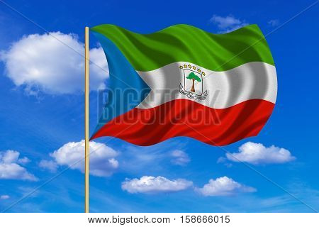 Equatorial Guinean national official flag. African patriotic symbol banner background. Correct colors. Flag of Equatorial Guinea on flagpole waving in the wind blue sky background. Fabric texture. 3D rendered illustration