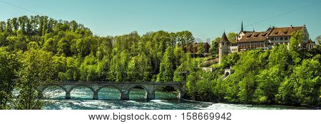 Panorama with medieval castle and bridge - Panorama on a sunny day with the Laufen Castle surrounded by forest and a stone bridge over the river Rhine in the Laufen-Uhwiesen town Switzerland