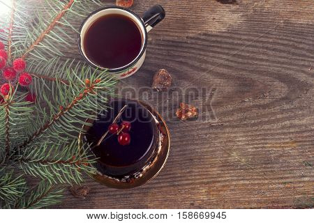 Happy Christmas cake with cup of tea and Christmas tree. Festive tea party. Copy space for text.