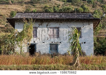 Nepali White Traditional House With Garden And Field Surrounding It, Himalayas, Nepal. Old Damaged A