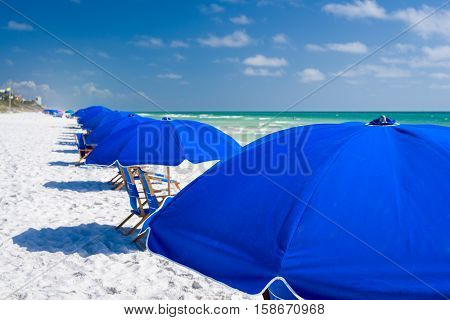 Group of blue beach umbrellas arranged in a row on a sunny day on one of Florida's Emerald Coast white sand beaches