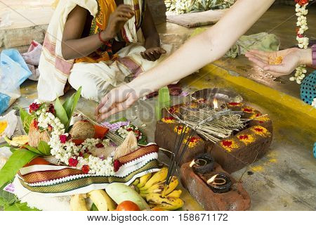 Documentary image. Pondichery, Tamil Nadu, India. May 27, 2014. Puja Thila homa with french lady and priest, brahman to pray about died man.