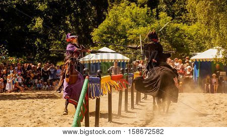 Two knights jousting riding in full speed on their horses breaking their lances against shields.
