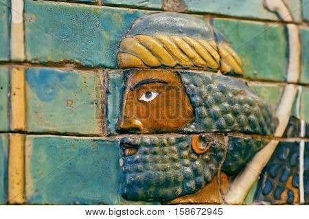 Face of ancient man ceramic patterned wall of city Babylon saved by Pergamon Museum in Berlin