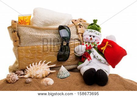 beach bag with towel, sunglasses, sun cream with a snowman in the sand on a white background