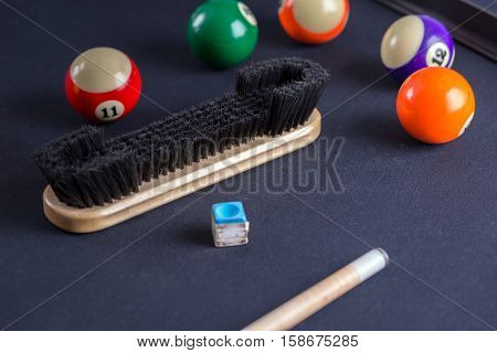 Brush for cleaning of billiard table with cue and balls.