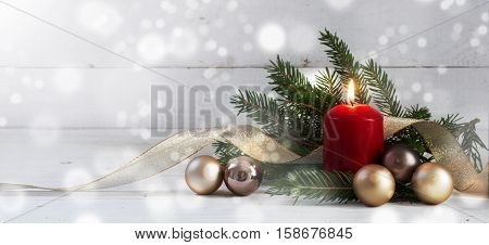 Red burning candle with christmas decoration fir tree baubles and golden ribbon in front of a white wooden wall with bokeh lights and generous copy space panorama selective focus narrow depth of field