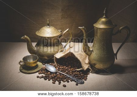 Heap of coffee beans in burlap sack with a vintage spoon and different vintage turkish coffeepots on canvas background.