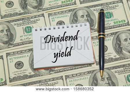 Notebook page with text DIVIDEND YIELD on dollar background