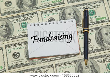 Notebook page with words FUNDRAISING on dollar background