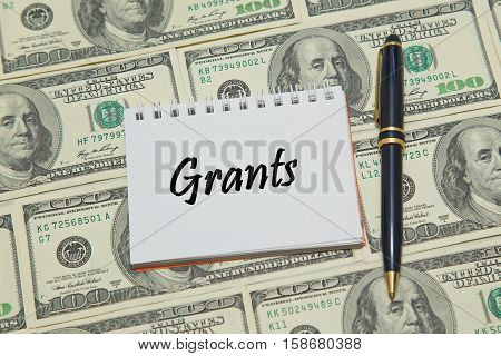 Notebook page with word GRANTS on dollar background