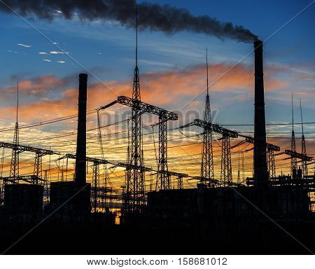 Smoke stacks at coal burning power plant industrial silhouette