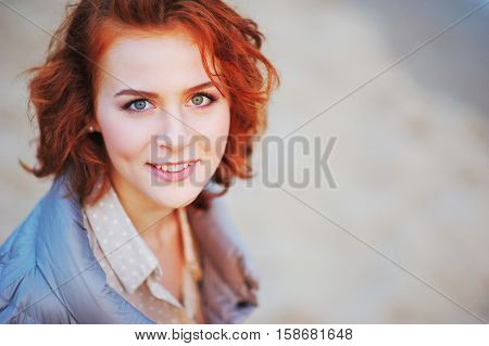 Young pretty woman with bright brown hair with mischievous eyes actually smiling on the street on blurred background, close up