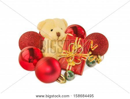 Teddy bear classic soft toy sitting with gift box and surrounded by red Christmas balls isolated over white. Christmas and New Year theme.