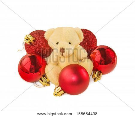 Teddy bear classic soft toy sitting with entourage of five red Christmas balls isolated over white. Christmas and New Year theme.