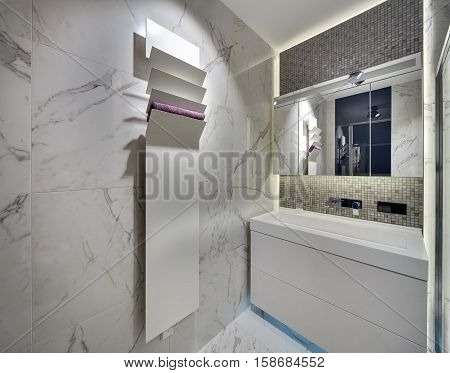 Modern bathroom with light tiles on the walls and the floor. There is a white sink  with a chrome faucet and a mirror, a white stand with a towel. Over the sink there is a mosaic wall. Horizontal.