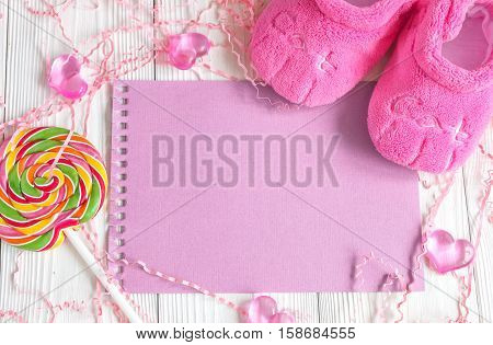 pink baby's bootees on wooden background top view
