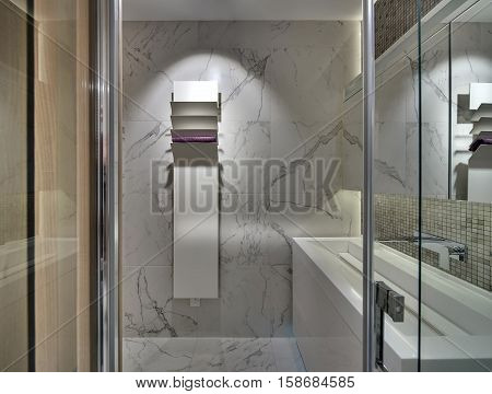 Contemporary bathroom with light tiles on the walls and the floor. There is a white sink  with a chrome faucet and a mirror, a white stand with a towel. Over the sink there is a mosaic wall.