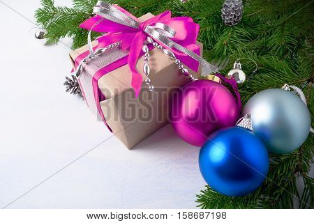 Christmas gift box with pink and blue ornaments. Christmas background with multicolored ornaments.