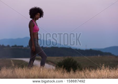 young African american woman runner with headphones jogging outdoors in nature beautiful summer night - Fitness, people and healthy lifestyle