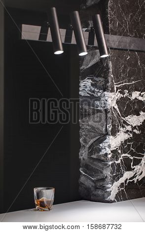 Textured black marble wall with white patterns and a white tabletop with a drink in a glass. There are three black glowing lamps on the wall. Closeup. Vertical.