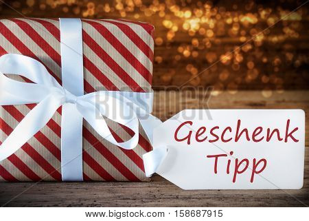 German Text Geschenk Tipp Means Gift Tip. Macro Of Christmas Gift Or Present On Atmospheric Wooden Background. Card For Seasons Greetings, Best Wishes Or Congratulations. White Ribbon With Bow.