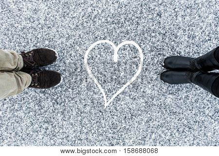 Male and Female boots standing at heart symbol on asphalt covered gritty snow surface. Rough snowy. Cold Winter. Top view. Relations concept