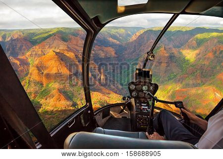 Helicopter cockpit flies in colorful Waimea Canyon State Park, also called Grand Canyon of Pacific, at sunset in Kauai, Hawaii, United States, with pilot arm and control board inside the cabin.