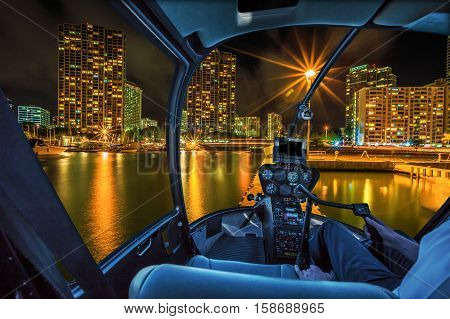 Helicopter cockpit flies in Ala Wai Harbor, Honolulu skyline by night, Oahu, Hawaii, with pilot arm and control board inside the cabin.