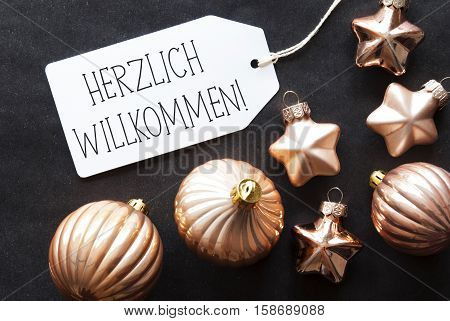 Label With German Text Herzlich Willkommen Means Welcome. Bronze Christmas Tree Balls On Black Paper Background. Christmas Decoration Or Texture. Flat Lay View