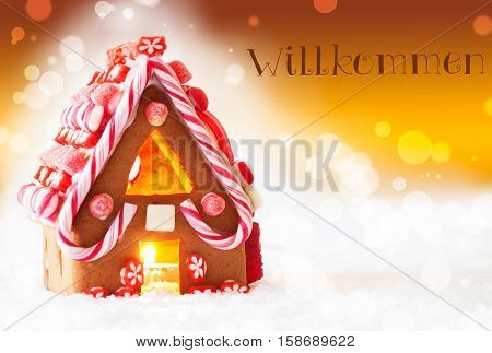 Gingerbread House In Snowy Scenery As Christmas Decoration. Candlelight For Romantic Atmosphere. Golden Background With Bokeh Effect. German Text Willkommen Means Welcome