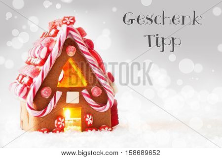 German Text Geschenk Tipp Means Gift Tip. Gingerbread House In Snowy Scenery As Christmas Decoration. Candlelight For Romantic Atmosphere. Silver Background With Bokeh Effect.