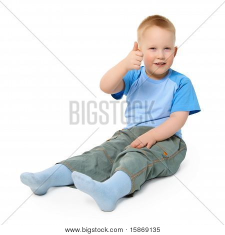 Little Boy Sits On White Background Showing A Gesture