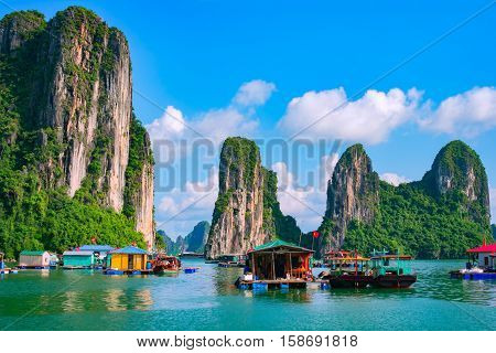 Floating fishing village and rock island in Halong Bay Vietnam Southeast Asia. UNESCO World Heritage Site. Junk boat cruise to Ha Long Bay. Landscape. Popular landmark famous destination of Vietnam